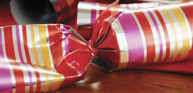 Holiday popper wrapped in silver paper with red, gold and pink stripes