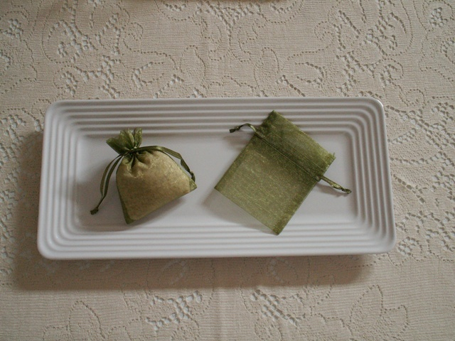 Basil sachets - scented with aromatherapy essential oil - in green organza bags on a white tray