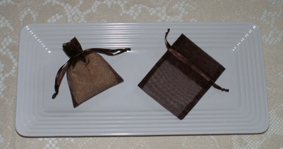 cinnamon sachets - scented with aromatherapy essential oil - in brown organza bags on a white tray