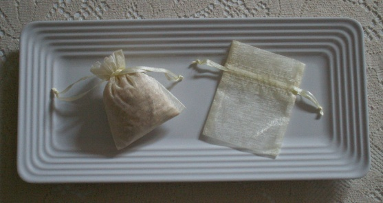 Lemon sachets - scented with aromatherapy essential oil - in soft yellow organza bags on a white tray