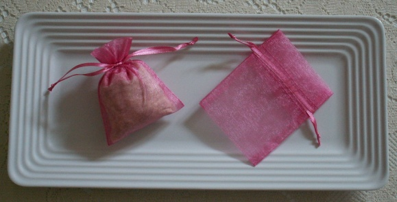 Pink Grapefruit sachets - scented with aromatherapy essential oil - in pink organza bags on a white tray